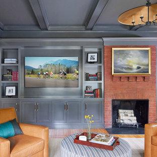 Ispirazione per un grande soggiorno chic chiuso con pareti blu, pavimento in legno massello medio, camino classico, cornice del camino in mattoni, parete attrezzata e pavimento marrone