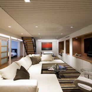 Aménagement d'une grande salle de séjour moderne fermée avec un mur blanc, un sol en liège, un téléviseur encastré, salle de jeu et un sol marron.
