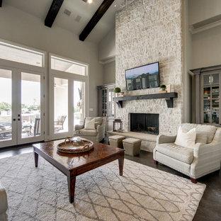 ダラスの広いビーチスタイルのおしゃれなオープンリビング (グレーの壁、濃色無垢フローリング、標準型暖炉、石材の暖炉まわり、壁掛け型テレビ) の写真