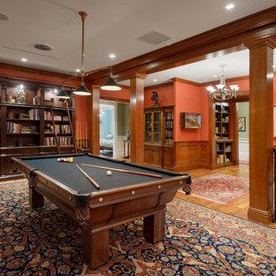 オーランドのトラディショナルスタイルのおしゃれなファミリールーム (ゲームルーム、赤い壁、無垢フローリング、茶色い床) の写真