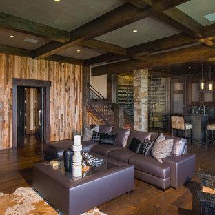 Idée de décoration pour une grande salle de séjour chalet ouverte avec un bar de salon, un sol en bois foncé, une cheminée d'angle, un manteau de cheminée en pierre, un téléviseur fixé au mur et un sol marron.