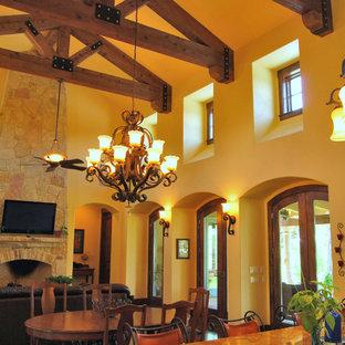 Ejemplo de sala de estar abierta, mediterránea, grande, con paredes beige, suelo de madera oscura, chimenea tradicional, marco de chimenea de piedra y televisor colgado en la pared
