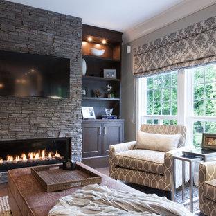 バンクーバーの大きいトラディショナルスタイルのおしゃれなファミリールーム (石材の暖炉まわり、グレーの壁、無垢フローリング、横長型暖炉、壁掛け型テレビ) の写真