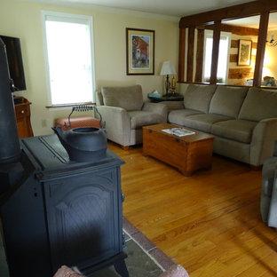 Diseño de sala de estar cerrada, tradicional, pequeña, con paredes amarillas, suelo de madera clara, estufa de leña, televisor en una esquina, suelo amarillo y marco de chimenea de metal