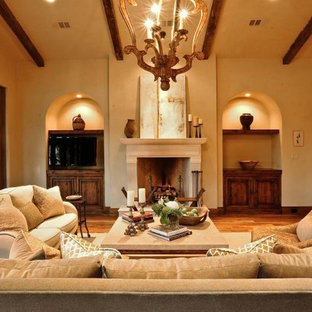Photo of a mid-sized mediterranean open concept family room in Other with beige walls, medium hardwood floors, a standard fireplace, a stone fireplace surround and a built-in media wall.