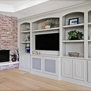 オレンジカウンティの広いコンテンポラリースタイルのおしゃれなオープンリビング (グレーの壁、淡色無垢フローリング、コーナー設置型暖炉、レンガの暖炉まわり、埋込式メディアウォール、ベージュの床、三角天井) の写真