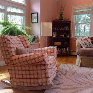 Imagen de sala de estar cerrada, campestre, de tamaño medio, sin chimenea, con paredes rosas, suelo de madera en tonos medios y televisor retractable