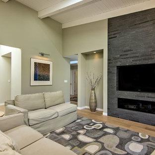 Idée de décoration pour une grand salle de séjour tradition ouverte avec un mur beige, un sol en bois brun, une cheminée ribbon, un manteau de cheminée en carrelage, un téléviseur fixé au mur et un sol marron.