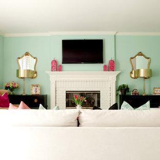 ロサンゼルスの中サイズのエクレクティックスタイルのおしゃれな独立型ファミリールーム (青い壁、無垢フローリング、標準型暖炉、レンガの暖炉まわり、壁掛け型テレビ、ベージュの床) の写真