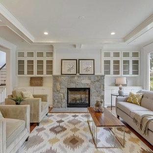 ワシントンD.C.の中サイズのトランジショナルスタイルのおしゃれなファミリールーム (グレーの壁、無垢フローリング、標準型暖炉、石材の暖炉まわり、壁掛け型テレビ、茶色い床) の写真