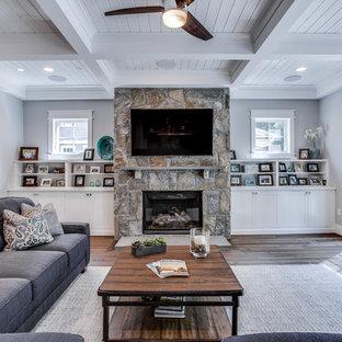 ワシントンD.C.の大きいおしゃれなファミリールーム (グレーの壁、無垢フローリング、標準型暖炉、石材の暖炉まわり、壁掛け型テレビ) の写真