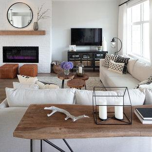 Foto de sala de estar abierta, de estilo de casa de campo, pequeña, con paredes blancas, suelo laminado, chimenea tradicional, marco de chimenea de ladrillo y televisor colgado en la pared