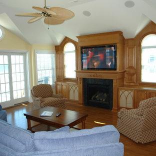 フィラデルフィアの大きいビーチスタイルのおしゃれなファミリールーム (ゲームルーム、黄色い壁、濃色無垢フローリング、標準型暖炉、木材の暖炉まわり、壁掛け型テレビ) の写真