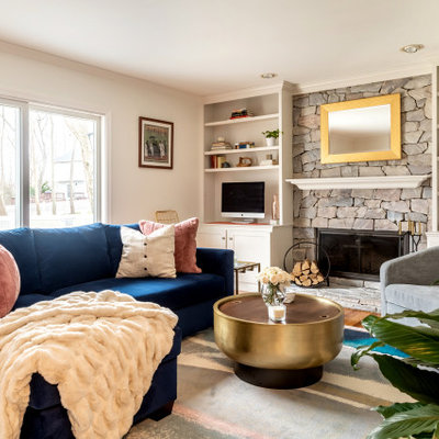 Transitional enclosed medium tone wood floor and brown floor family room photo in New York with white walls, a standard fireplace, a stone fireplace and a media wall