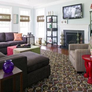 ワシントンD.C.の中サイズのエクレクティックスタイルのおしゃれなファミリールーム (青い壁、濃色無垢フローリング、標準型暖炉、漆喰の暖炉まわり、壁掛け型テレビ、茶色い床) の写真