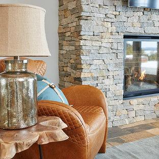 グランドラピッズの中サイズのビーチスタイルのおしゃれなファミリールーム (グレーの壁、スレートの床、標準型暖炉、石材の暖炉まわり、壁掛け型テレビ) の写真