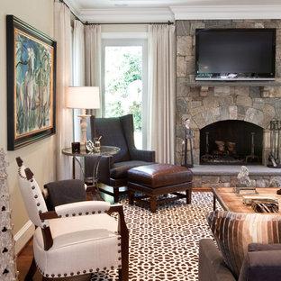 Modelo de sala de estar tradicional con paredes beige, suelo de madera oscura, chimenea tradicional, marco de chimenea de piedra y televisor colgado en la pared