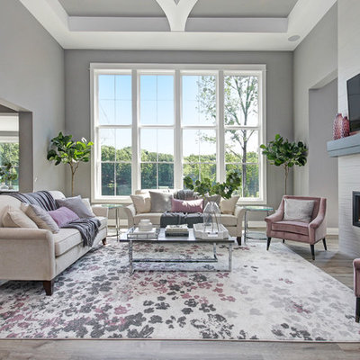 Transitional open concept light wood floor family room photo in Grand Rapids with gray walls, a ribbon fireplace, a tile fireplace and a wall-mounted tv