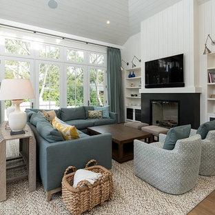 サンフランシスコの中サイズのビーチスタイルのおしゃれなファミリールーム (白い壁、無垢フローリング、標準型暖炉、金属の暖炉まわり、壁掛け型テレビ、茶色い床) の写真