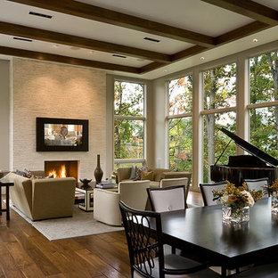 Réalisation d'une salle de séjour design ouverte avec un mur beige, un sol en bois foncé, une cheminée standard, un manteau de cheminée en pierre et un téléviseur fixé au mur.