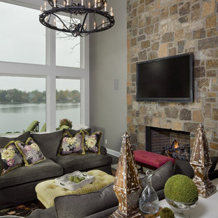 Transitional family room photo in Indianapolis with gray walls, a standard fireplace, a stone fireplace and a wall-mounted tv