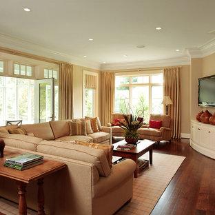 Idee per un soggiorno classico con pareti beige, pavimento in legno massello medio e porta TV ad angolo