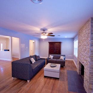 Idee per un grande soggiorno design aperto con pareti blu, camino classico, cornice del camino in pietra e TV nascosta
