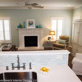 他の地域の中サイズのビーチスタイルのおしゃれなファミリールーム (青い壁、カーペット敷き、標準型暖炉、レンガの暖炉まわり、内蔵型テレビ) の写真