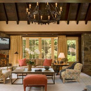 Ejemplo de sala de estar clásica, de tamaño medio, con paredes beige, moqueta, chimenea de esquina, marco de chimenea de piedra y televisor colgado en la pared