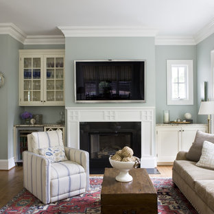 Example of a classic medium tone wood floor family room design in DC Metro with gray walls, a standard fireplace and a wall-mounted tv