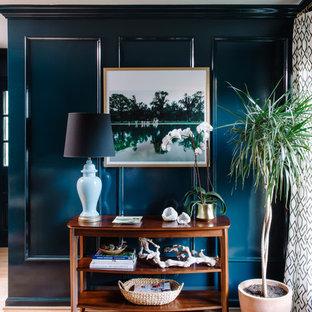 Diseño de sala de estar cerrada, ecléctica, pequeña, con paredes azules, suelo de madera clara, chimenea tradicional, marco de chimenea de madera y televisor colgado en la pared