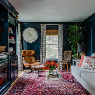 Imagen de sala de estar cerrada, ecléctica, pequeña, con paredes azules, suelo de madera clara, chimenea tradicional, marco de chimenea de madera y televisor colgado en la pared