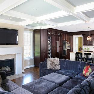 Ejemplo de sala de estar abierta, tradicional, grande, con paredes beige, suelo de madera oscura, chimenea tradicional, televisor colgado en la pared y marco de chimenea de piedra