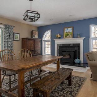 ブリッジポートの中サイズのおしゃれなファミリールーム (青い壁、淡色無垢フローリング、標準型暖炉、木材の暖炉まわり、壁掛け型テレビ、ベージュの床) の写真
