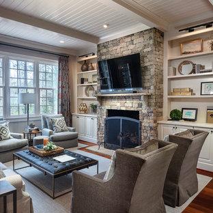 Imagen de sala de estar abierta, clásica, de tamaño medio, con paredes blancas, chimenea tradicional, marco de chimenea de piedra, televisor colgado en la pared, suelo marrón y suelo de madera oscura