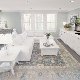 ポートランドの広いトランジショナルスタイルのおしゃれな独立型ファミリールーム (青い壁、淡色無垢フローリング、コーナー設置型暖炉、タイルの暖炉まわり、据え置き型テレビ、グレーの床) の写真