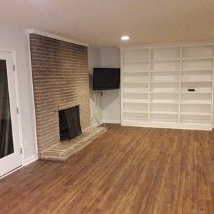 デトロイトの広いコンテンポラリースタイルのおしゃれなオープンリビング (白い壁、淡色無垢フローリング、標準型暖炉、レンガの暖炉まわり、コーナー型テレビ、茶色い床) の写真