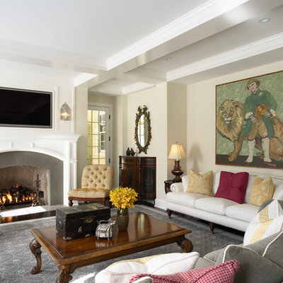 Family room - mid-sized traditional enclosed family room idea in Minneapolis with beige walls, a standard fireplace, a wall-mounted tv and a stone fireplace