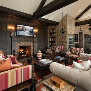 Ejemplo de sala de estar abierta, mediterránea, grande, con paredes marrones, chimenea tradicional, televisor colgado en la pared y marco de chimenea de baldosas y/o azulejos