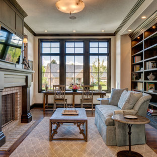 Example of a large classic open concept medium tone wood floor and brown floor family room design in Salt Lake City with beige walls, a standard fireplace, a brick fireplace and a wall-mounted tv