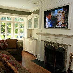 ニューヨークの中サイズのトラディショナルスタイルのおしゃれな独立型ファミリールーム (ホームバー、緑の壁、無垢フローリング、標準型暖炉、木材の暖炉まわり、埋込式メディアウォール、茶色い床) の写真
