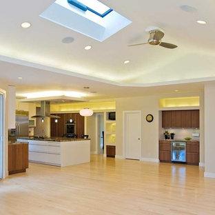 Ispirazione per un ampio soggiorno moderno aperto con pareti beige, parquet chiaro, camino classico e cornice del camino in mattoni