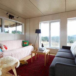 Cette photo montre une salle de séjour tendance avec un mur beige, un sol en contreplaqué et aucun téléviseur.