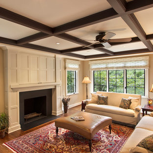 Elegant dark wood floor family room photo in DC Metro with beige walls, a standard fireplace and a concealed tv