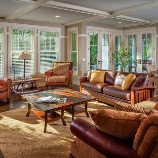 Exemple d'une grand salle de séjour craftsman ouverte avec un mur beige, un sol en bois brun, une cheminée standard, un manteau de cheminée en pierre et aucun téléviseur.