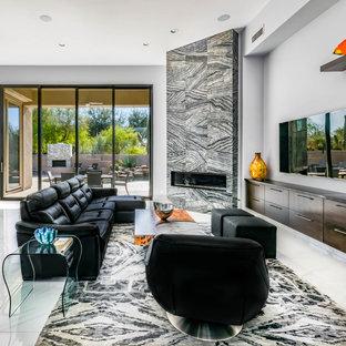 Immagine di un grande soggiorno tradizionale aperto con pareti grigie, pavimento in marmo, camino ad angolo, cornice del camino piastrellata e TV a parete