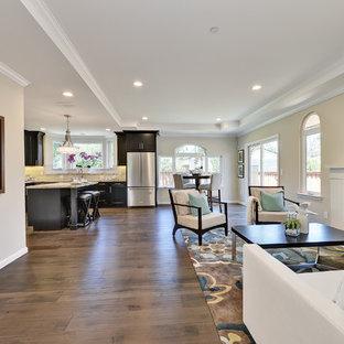 Foto di un soggiorno tradizionale con pareti beige, pavimento in compensato e pavimento marrone