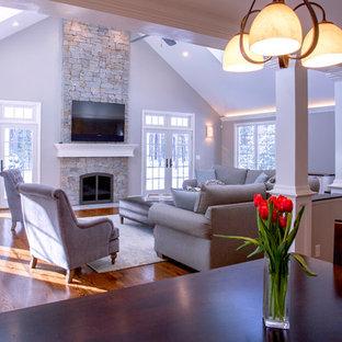 Esempio di un ampio soggiorno tradizionale aperto con pareti grigie e pavimento in legno massello medio