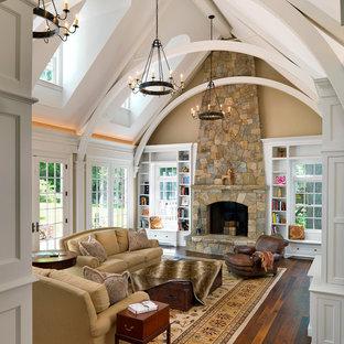 ボストンのトラディショナルスタイルのおしゃれなファミリールーム (ベージュの壁、濃色無垢フローリング、標準型暖炉、石材の暖炉まわり) の写真