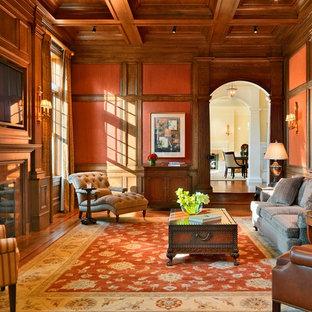 Idee per un soggiorno classico chiuso con pareti arancioni, pavimento in legno massello medio, camino classico e TV a parete